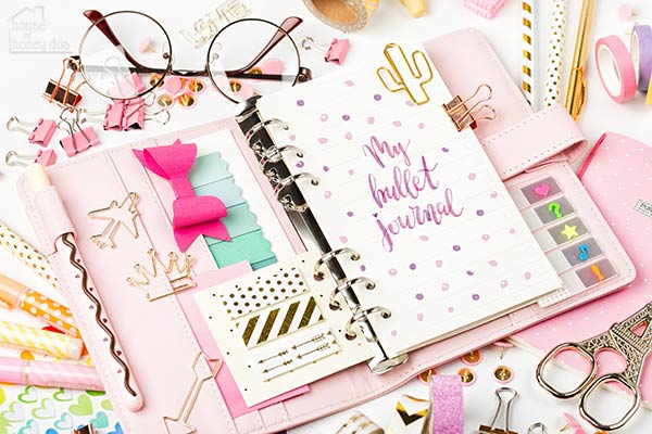 desk with pink planner, stickers, paper clips, and other accessories